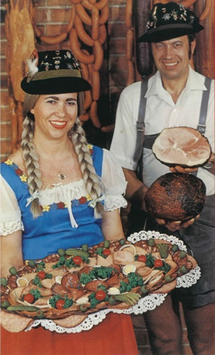 woman and man holding sausages and hams